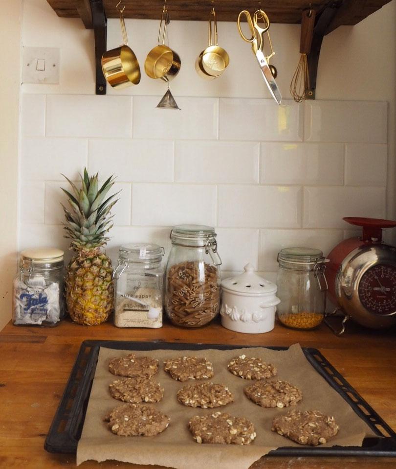 Kitchen worktop with gold utensils, nutribuddy gluten-free breakfast shake and oat cookies