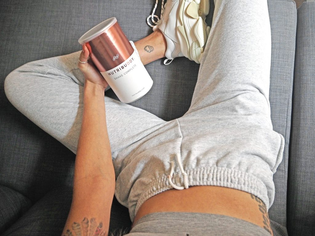 Woman in grey jogging bottoms holding a tub of Nutribuddy Shake Complete