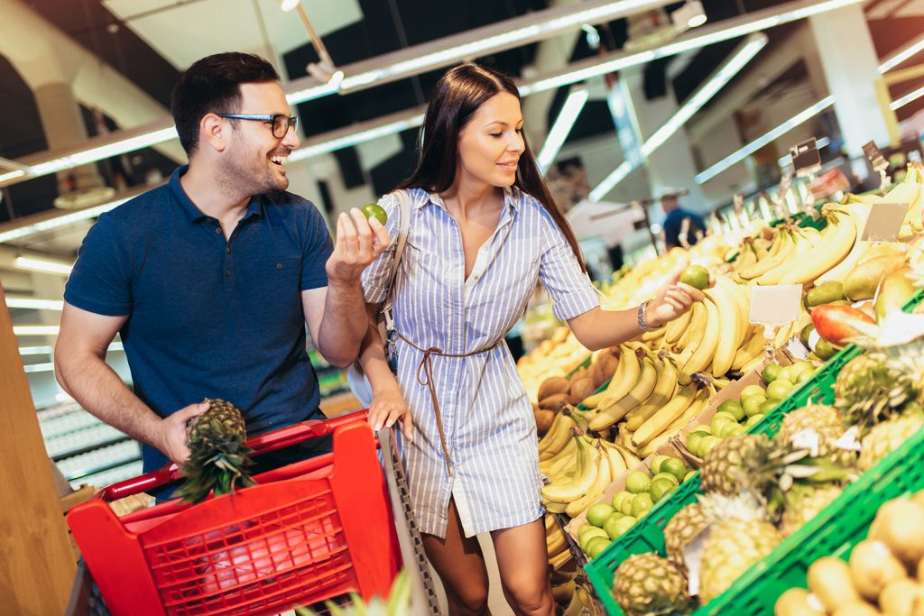 couple in supermarket buying fresh fruit