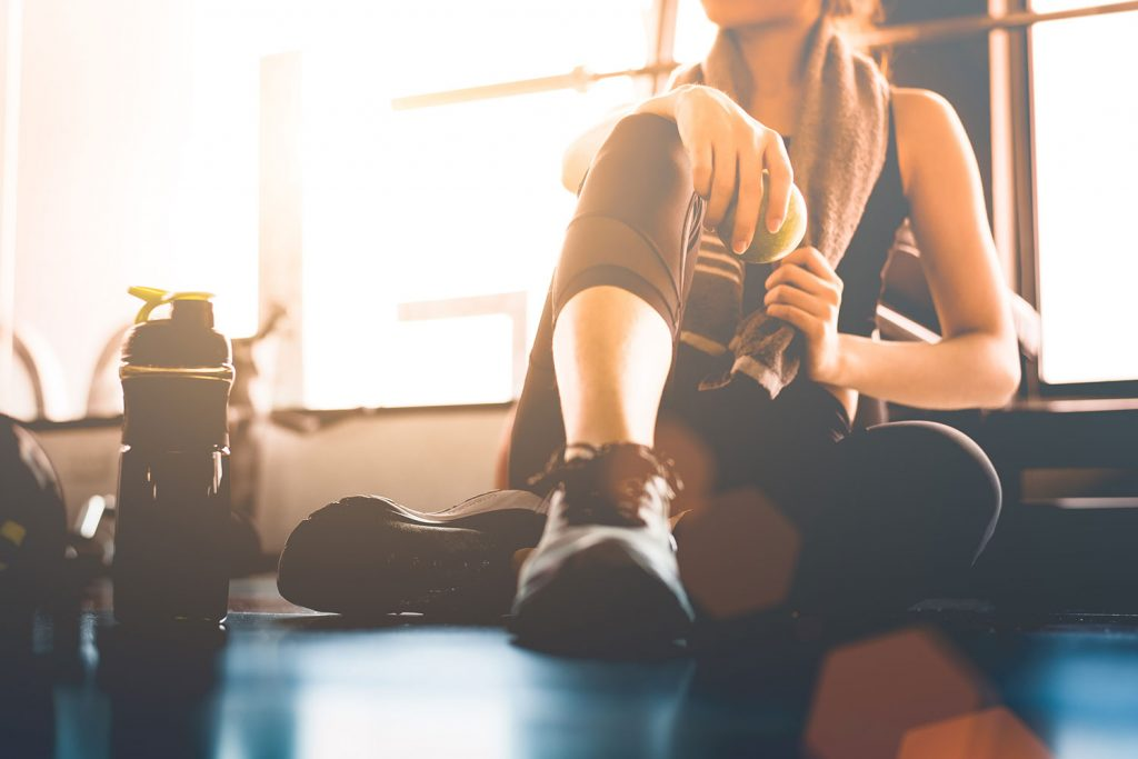 woman exercising at the gym with a meal replacement shake